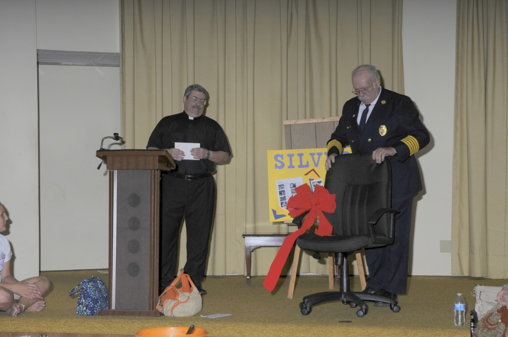 Pastor Kendall receiving his new office chair from Fire Chief George Gettler